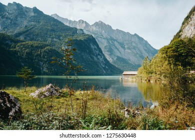 Lake Obersee in scenic National park Berchtesgadener. Traditional wooden boat house on the shore of the lake and mountains with green forest, Bavaria, Germany.