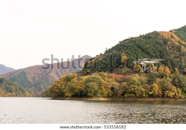 Lake Okutama and hovering drone in autumn