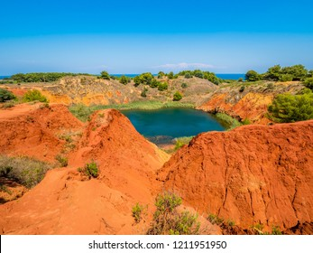 The lake in a old bauxite's red soils quarry cave in Apulia, Otranto, Salento, Italy. The digging was filled with natural waters.