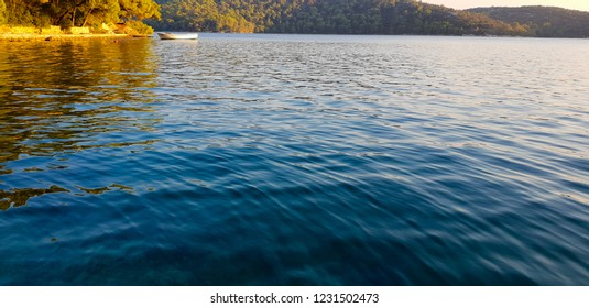 Lake on the island Mljet in the golden evening sunshine, green trees around and deep blue water, one boat on the calm surface, Croatiq, high season