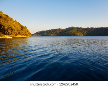 Lake on the island Mljet in the golden evening sunshine, green trees around and deep blue water, one boat on the calm surface, Croatia high season