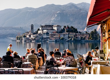 LAKE ORTA, ITALY - FEB 24: People in a restaurant in Orta on February 24, 2012. With the nearby Unesco site Sacro Monte and San Giulio island, Orta is a popular destination for small-scale tourism.