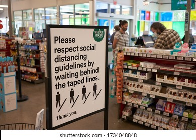 Lake Oswego, OR, USA - May 15, 2020: The sign at the checkout area in a Whole Foods Market reminds shoppers to respect social distancing guidelines by waiting behind the taped lines on the floor.