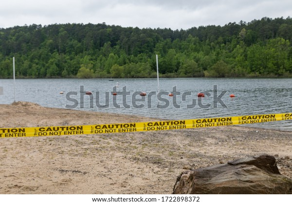 lake ouachita state park, Arkansas, USA, May 2 2020, Campgrounds opened for residents of the state but restrooms  beach and playground areas remain closed. Yellow caution tape and signs.
