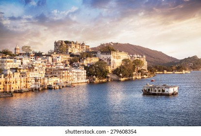 Lake Pichola with City Palace view at cloudy sunset sky in Udaipur, Rajasthan, India