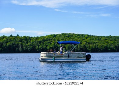 LAKE PLACID, NEW YORK - AUGUST 20, 2020: Boaters on pontoon boat enjoy summer day on Lake Placid in New York State's Adirondack Mountains