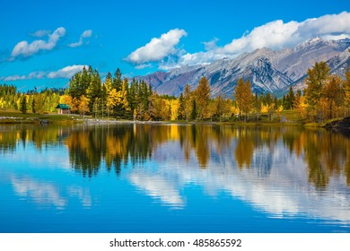 The lake, red-orange trees  and mountains.. Bright shining day in the Canadian Rockies. Canmore, near Banff. Concept of hiking