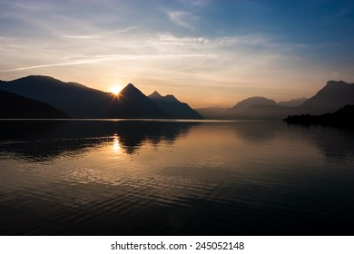 Lake reflection on a beautiful summer morning, in the Swiss Alps. Buochs, Switzerland.