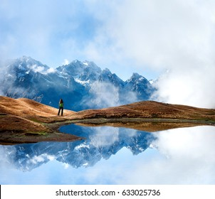 Lake with reflection of the rocky ridge covered with snow and young woman enjoying the view. Beautiful landscape from Svaneti, Georgia, Europe.