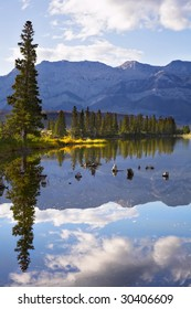 Lake, reflections of clouds and fur-trees and mountains in the distance