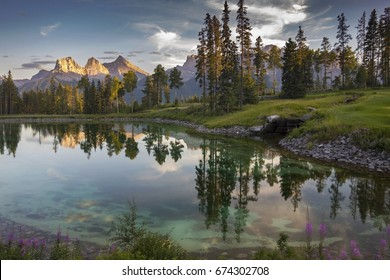 Lake Reflections in Famous Silvertip Golf Course above Town of Canmore with Distant Landscape View of Three Sisters Mountain in Alberta Foothills near Banff National Park