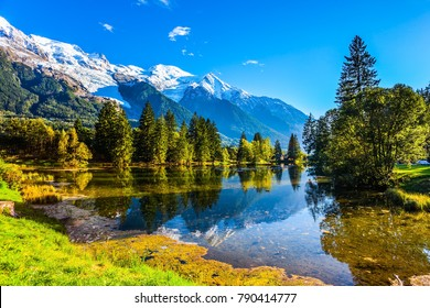 The lake reflects the forest and the blue sky. Chamonix City Park is illuminated by sunset. Sunny autumn day in the French Alps. Concept of active winter tourism