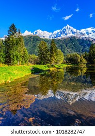 The lake reflects the snowy mountains, the forest and the blue sky. Chamonix City Park is illuminated by sunset. Wonderful autumn day in the French Alps. Concept of active winter touris