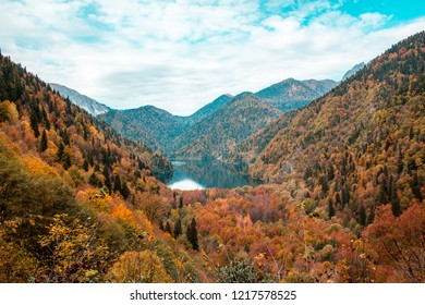 Lake Ritsa, Abkhazia, autumn 2018. Mountain lake in a mountain forest. Solitude, tranquility, autumn landscape, forest and red trees, beautiful background, bright colors of autumn