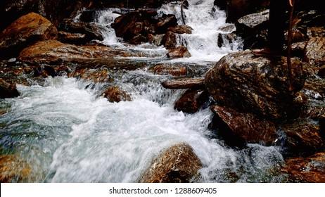Lake river water stream with mountain rocks, location is Kasol, Himachal Pradesh, India.
