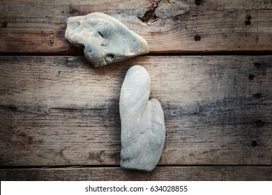 Lake rocks in the shape of the state of Michigan on a wooden background