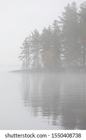 Lake scape and foggy opposite shore forest at dawn