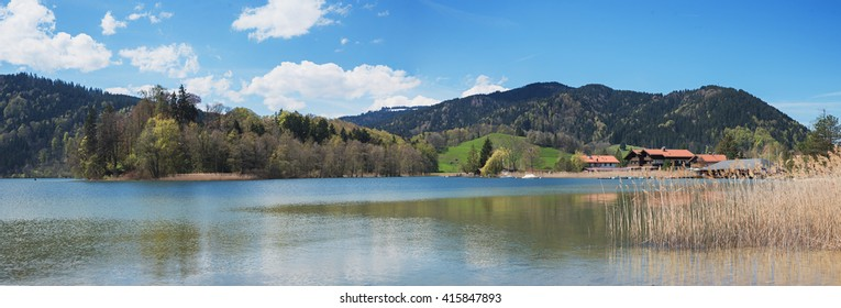 lake schliersee with springlike hills and boathouses, bavarian landscape