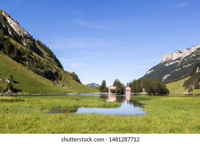 Lake Seealpsee with wetland at the foreground and house reflection in the valley of Ebenalp, Appenzellerland, Switzerland