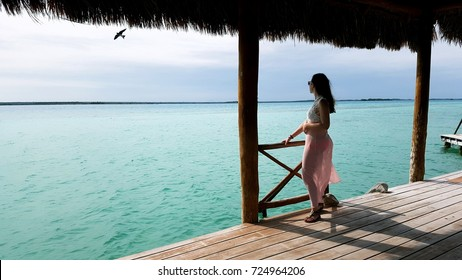 Lake of the seven colors in Bacalar  (Mexico). A young woman standing at a balcony and is observing the water. Bird flying through the picture at this moment.