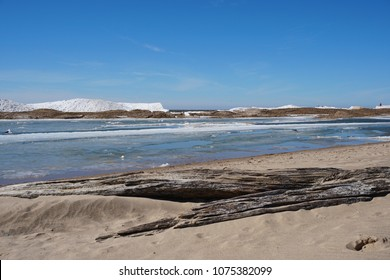 Lake shore on spring day with ice and snow in water, blue sky in the background, driftwood in foreground