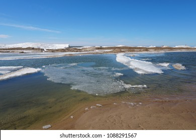 Lake shore on spring day with ice and snow in water, blue sky in the background, sandy beach in foreground