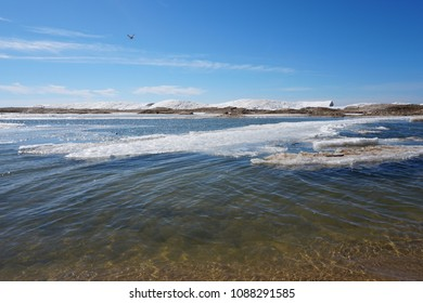 Lake shore on spring day with ice and snow in water, blue sky in the background