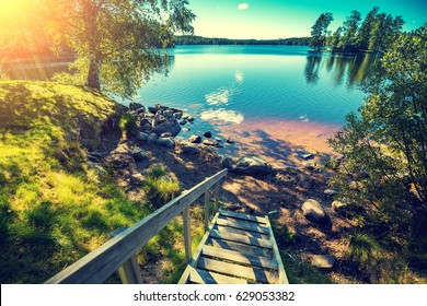 Lake shore with trees and wooden stairway. Beautiful nature Finland.
