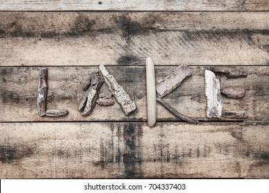 Lake sign made of driftwood on a wooden background