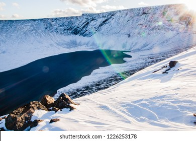 Lake in snowy mountains in sunny day. Sunspots. Khibiny mountains, Murmansk region, Russia.