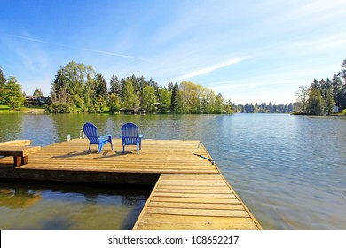 Lake spring waterfront with pier and two blue chairs.