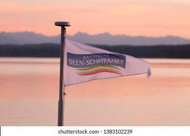 "LAKE STARNBERG, BAVARIA / GERMANY - September 11, 2018: Flag with writing ""Bayerische Seen-Schifffahrt"" waving on a boat / damper at Lake Starnberg. In the back: the silouettes of the alpine mountains"