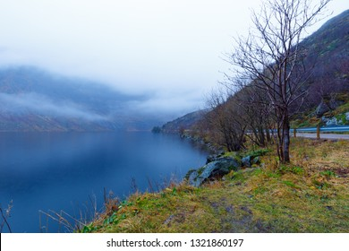 Lake Storvatnet in Norway on cloudy days with mountains in background, covered in fog in fall