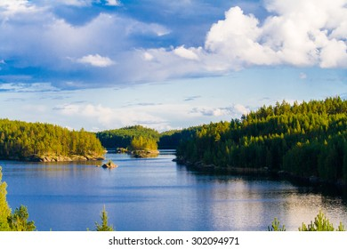 Lake summer view with reflection of clouds on water surface, Finland