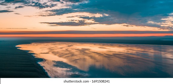 Lake at sunset from above, a beautiful pink sky with clouds reflected in the water. The salt lake Manych-Gudilo, Russia.