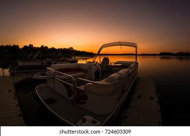 Lake sunset featuring docked pontoon boat
