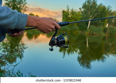 Lake at sunset. A fisherman on the  bank. Fishing rod wheel closeup. Spinning reel. The concept of outdoor activities. Tackles for pike, perch, zander.