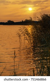 A lake at sunset on lovely midsummer evening with some electricity poles in the background