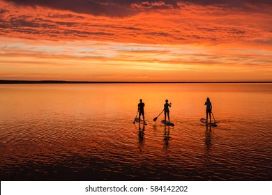 lake sup surfing under amazing red sunset sky with three people