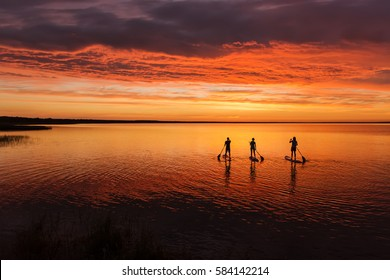 lake sup surfing under amazing dark sunset sky with three people