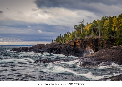 Lake Superior Coast, Gray sky and stormy seas crash on the cliffs of the black rocks along the shores of the Lake Superior coast. Presque Isle Park. Marquette, Michigan.