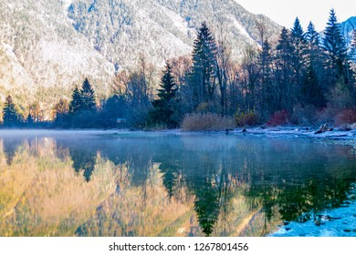 The lake is surrounded by beautiful mountains, mountains, pines, trees, spring, fog over the water