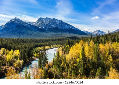 The lake is surrounded by colorful autumn forest. The picturesque Abraham lake in the mountain valley of the Rockies of Canada. Concept of active, ecological and photo tourism