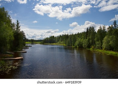 Lake surrounded by forest in a beautiful sunny day. Landscape with blue sky and white clouds.