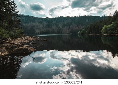 Lake surrounded by mountains with beautiful clouds on Sumava