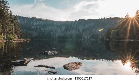Lake surrounded by mountains with shining sun on Sumava