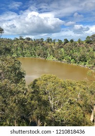 Lake surrounded by trees and bushland with clouds and blue sky in background in country