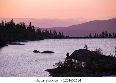 Lake surrounded with forest, rocks and mountains. Beautiful view of pink sky, landscape in dusk. Norway, Kongsberg