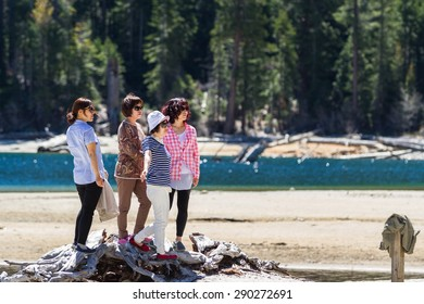 Lake Tahoe, California - April 29 : Asian tourists posing for a picture on the shore of Emerald Bay, April 29 2015 Lake Tahoe, California.