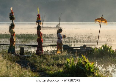 Lake Tamblingan, Tabanan, Bali, Indonesia - May 12, 2017 : Small procession of Balinese women going to the temple in the early morning
